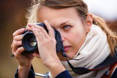 Pretty female amateur photographer taking photos outdoors, doing - stock photo