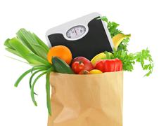 Fresh groceries in a paper bag with weight scale Stock Photos