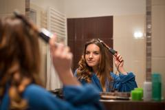 Pretty, young woman curling her hair in front of her bathroom mi - stock photo