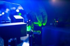 Quantum optics - hand of a researcher adjusting a laser beam in Stock Photos