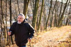 Senior man nordic walking, enjoying the outdoors, the fresh air, Stock Photos