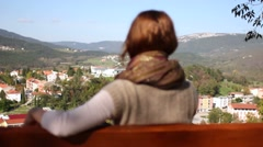 Nice girl on a bench enjoying the panorama and setting her hair Stock Footage