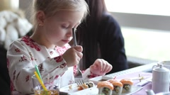 Little girl eats sushi with a fork - stock footage