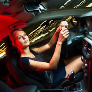 Driving a car at night - pretty, young woman driving her modern Stock Photos