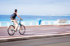 Great way to get around in a city -Motion blurred cyclist going Stock Photos