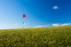 Red golf flag on a golf course, moving in the wind (motion blurr - stock photo
