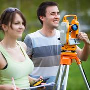 Two young land surveyors at work Stock Photos