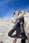 Stock Photo of View from below of a climber while climbing a steep rock wall