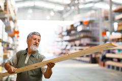 Man buying construction wood in a  DIY store for his DIY home re - stock photo