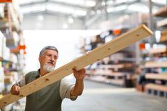 Man buying construction wood in a  DIY store for his DIY home re Stock Photos