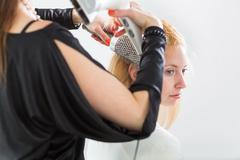 Hairdresser/Hairstyle artist working on a young woman's hair, gi - stock photo