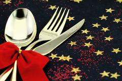 Christmas cutlery. Spoon, fork and knife stacked up on a starry background - stock photo