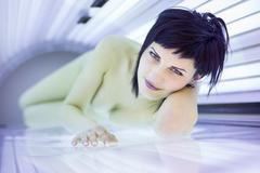 Pretty young woman tanning her skin in a modern solarium Stock Photos