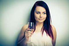 Stock Photo of Pretty, young woman having a glass of wine (color toned image)
