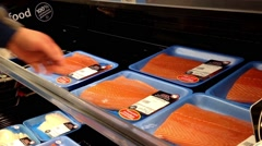 Man selecting atlantic salmon fillet inside Walmart store Stock Footage