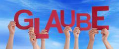People Holding German Word Glaube Means Belief Blue Sky - stock photo