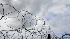Barbed wire  trembling in the wind on the  dark stormy clouds background Stock Footage