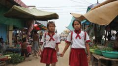 Uniformed schoolchildren in poor Asian street market - stock footage