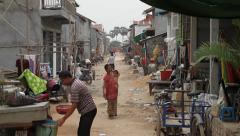 Woman and child walking in Asian slum market street Stock Footage