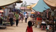 Small girl walks down Asian slum market street Stock Footage