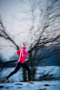 Winter running - Young woman running outdoors on a cold winter d Stock Photos