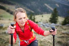 Pretty, young female hiker having a tough walk uphill - stock photo