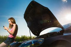 Stock Photo of Pretty, young woman calling the roadside service/assistance afte