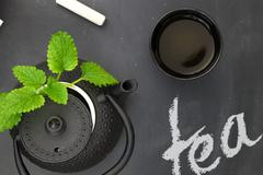 Teapot with herbs and teacup on chalkboard top shot - stock photo