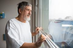 Patient at a hospital, looking from a window in his room, doing Stock Photos
