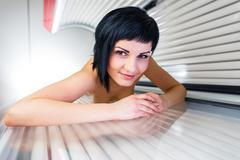 Pretty, young woman tanning her skin in a modern solarium/sunbed Stock Photos