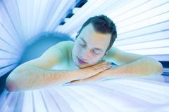 Handsome young man relaxing during a tanning session in a modern Stock Photos