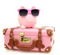 Pink suitcase with piggy bank in sunglasses isolated Stock Photos