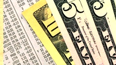 Close-up of newspaper financial information, U.S. dollars and Go board. Stock Footage
