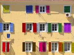 Colorful windows with louvered shutters Stock Photos