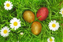 Easter background with grass, flowers and colorful glitter eggs - stock photo
