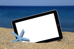 Promotional tablet template on the beach - stock photo
