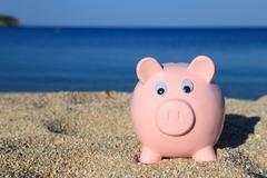 Stock Photo of Summer piggy bank on the beach