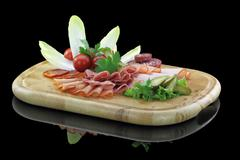 Meat delicatessen plate with vegetables - stock photo