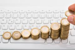 Close-up Of Person Stacking Coins On Computer Keyboard - stock photo