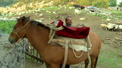 Man takes off saddle from his horse after riding on the mountain village Stock Footage
