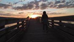walking along a bridge at sunset - stock footage