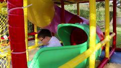 Boys are going down the tube slide at the playground Stock Footage