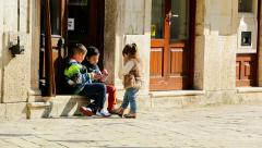 Boys and girl playing on the cobbled streets of the old town Stock Footage
