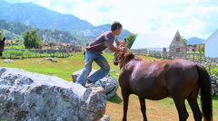 Boy jumping on the horse and riding on the mountain village slow motion - stock footage