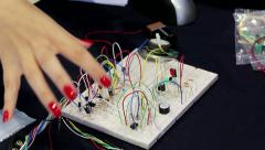 Young woman shows how to connect and install the wires and diodes on the board Stock Footage