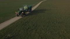 Huge tractor with trailer, spreading liquid manure. Panoramic view of City Basel Stock Footage