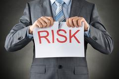 Stock Photo of Businessman Tearing The Word Risk On Paper Over Gray Background