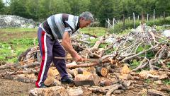 Stock Video Footage of Man is splitting wood with axe in the countryside