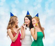 smiling women in party caps blowing to whistles - stock photo