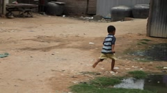 Little boy runs into slum home Cambodia Stock Footage